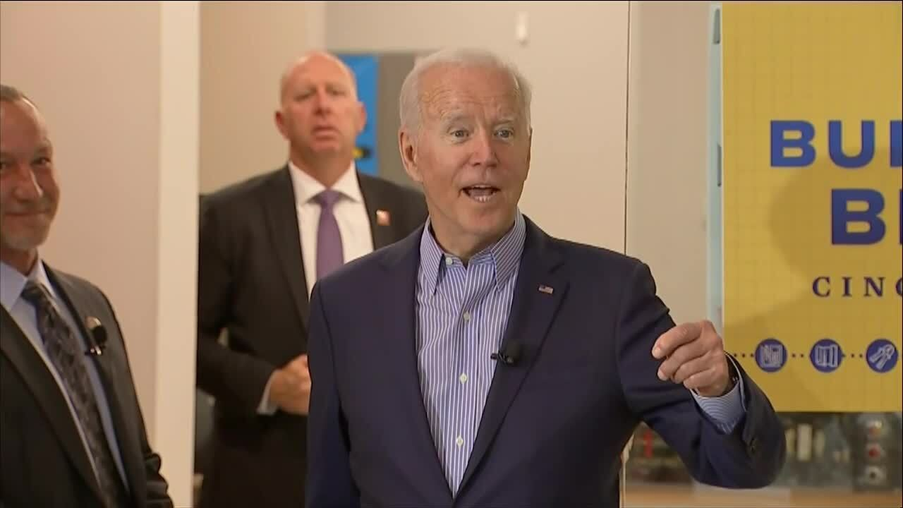 """A caucasian man in a gray suit stands next to President Joe Biden, wearing a navy blue suit and striped shirt, next to a blue and yellow sign that reads """"Build Back Better: Cincinnati, OH."""""""