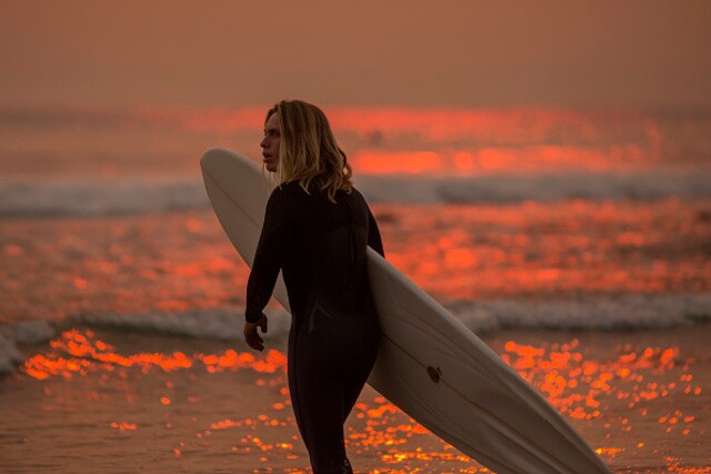 Surfers in Carpinteria paddle out to smoke-filled skies