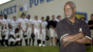 """FILE - In this Sept. 19, 2003 file photo James """"Radio"""" Kennedy stands with the T.L. Hanna High School varsity football team behind him just before Friday night's game against Fort Mill in Fort Mill, S.C. Kennedy, the man who was a fixture on the sidelines of the South Carolina high school's football games for decades and whose life inspired a Hollywood movie, died Sunday, Dec. 15, 2019. He was 73. (Amber M. McCloskey/The Herald via AP, File)"""