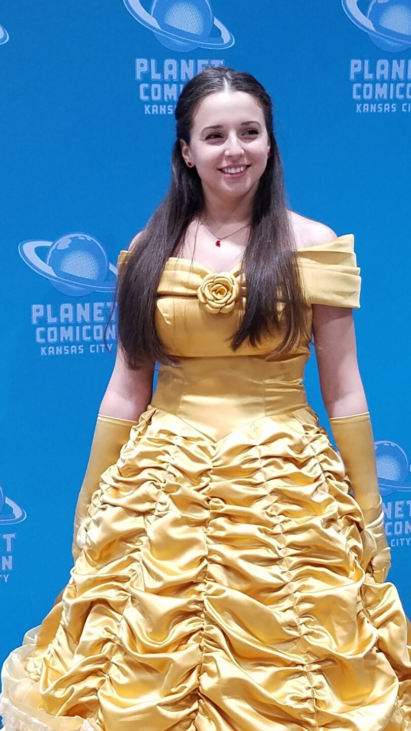 A cosplayer dressed as Belle from Beauty and the Beast.