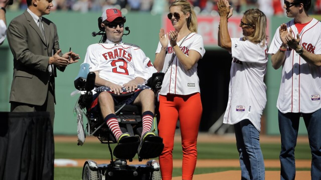 FILE - In this April 13, 2015, file photo, Pete Frates, former Boston College baseball player whose Ice Bucket Challenge raised millions for ALS research, is applauded by Boston Red Sox general manager Ben Cherington, far left, and his wife Julie Frates, center, along with other family members prior to the home opener baseball game between the Boston Red Sox and the Washington Nationals at Fenway Park in Boston. Frates, who was stricken with amyotrophic lateral sclerosis, or ALS, died Monday, Dec. 9, 2019. He was 34. (AP Photo/Elise Amendola, File)
