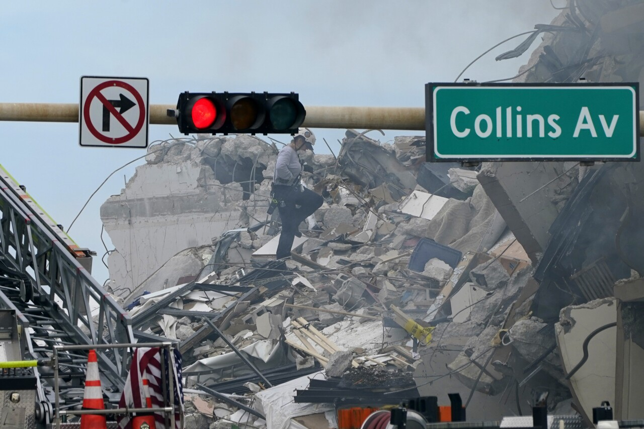 Rescuer walks on rubble after Champlain Towers South condo collapse, June 24, 2021