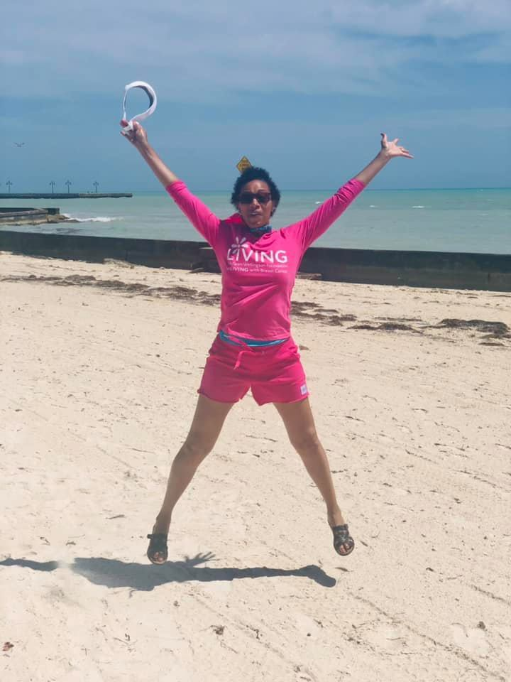 Sherry Hughes in a photo taken in April 2021 during a trip with her husband. The photo shows her jumping in the air as she's wearing a pink long-sleeved shirt and pink shorts.