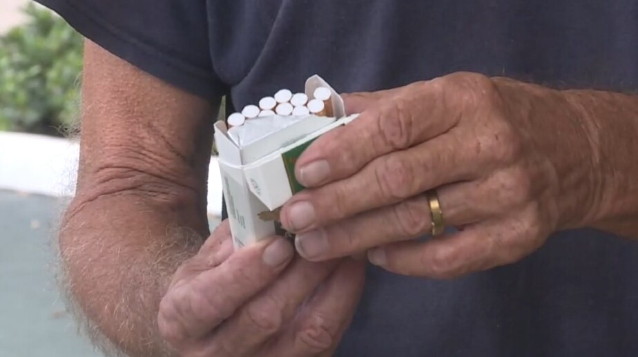 Tom Thompson of Deerfield Beach opens a pack of cigarettes on July 9, 2021.jpg