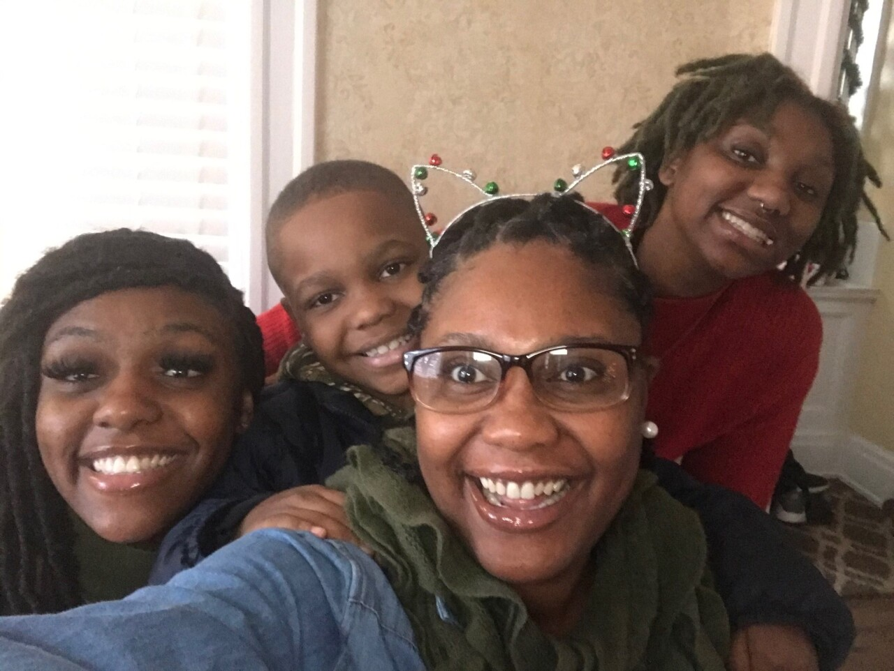 LaTasha Hambrick, second from right, smiles in this selfie with her son and two daughters. Hambrick is wearing glasses and a cat ear hairband.