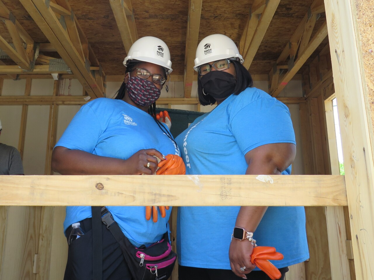 Shelisa Gilmore, left, and Vera Suggs, right, pose with masks pulled above their nose and mouth in this photo as they stand next to each other inside the Bond Hill duplex they are helping to build.