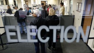In this Oct. 8, 2018, file photo, local residents wait in line for their ballot at the Polk County Election office on the first day of early voting for the Iowa general election in Des Moines, Iowa. An Iowa judge has struck down as unconstitutional large portions of a 2017 voting reform law challenged by a Hispanic civil rights group and an Iowa State University student. (AP Photo/Charlie Neibergall)