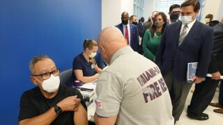 Gov. Ron DeSantis watches as Carlos Dennis receives COVID-19 vaccine in Miami, Jan. 6, 2021