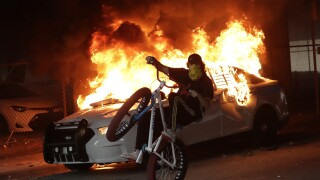 Protester on bicycle rides past burning Miami police car during protests, May 30