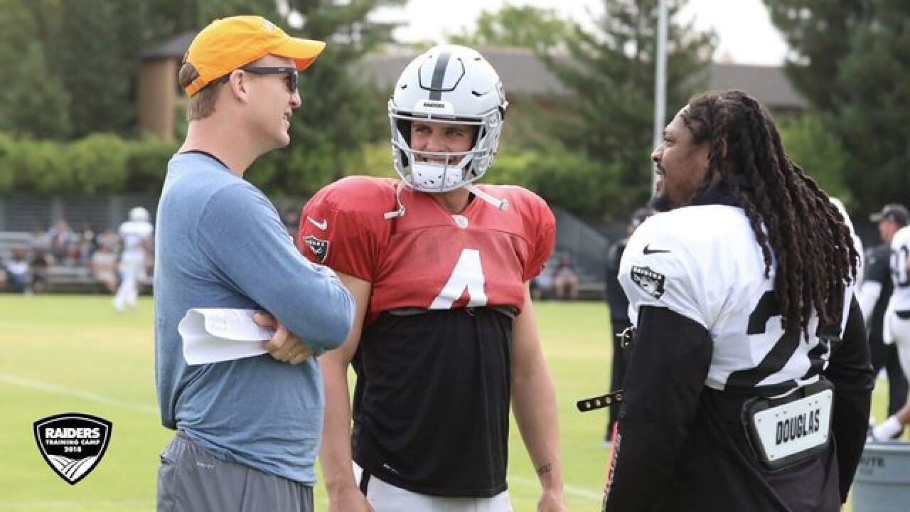 Peyton Manning chatted with players and coaches and went over techniques at Raiders training camp