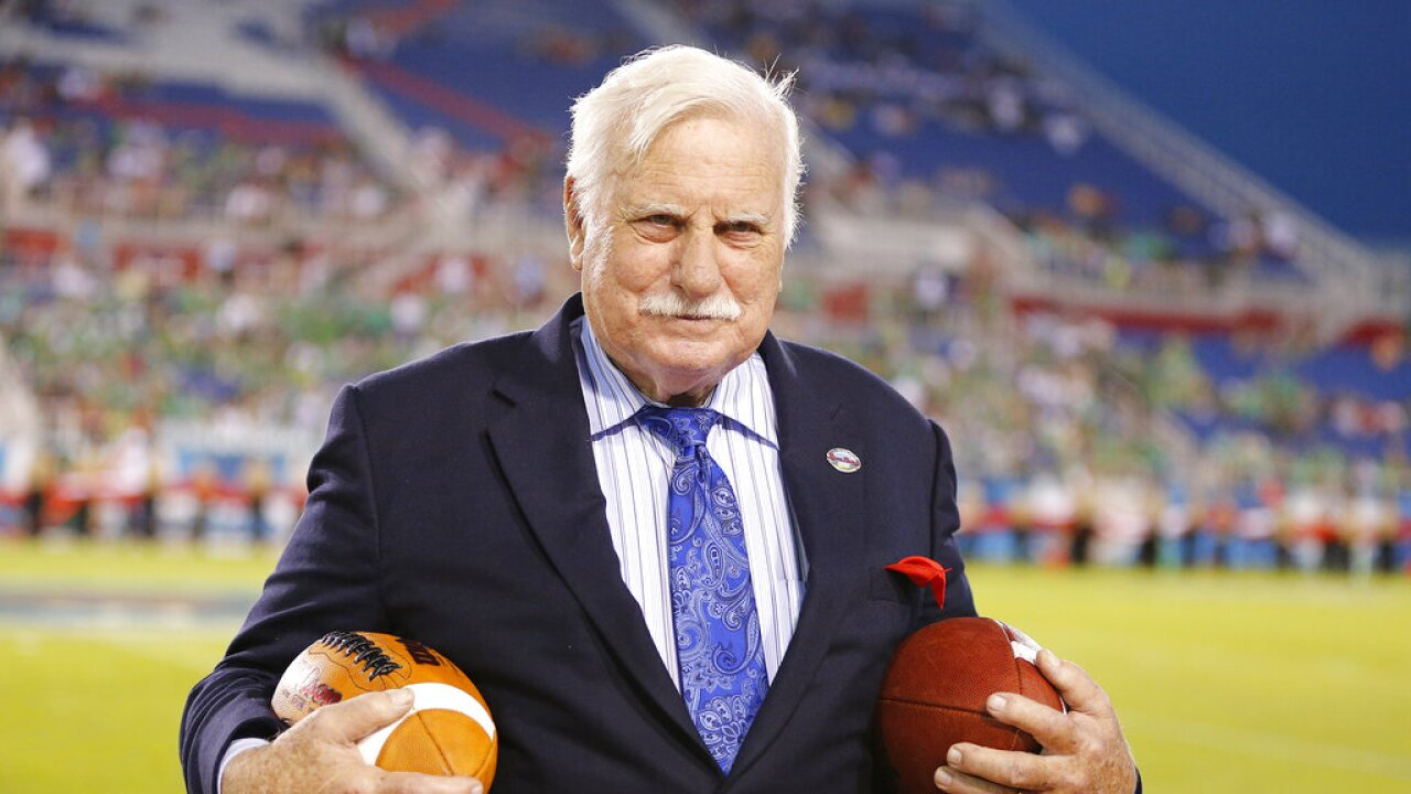 Howard Schnellenberger holding footballs before 2014 Boca Raton Bowl