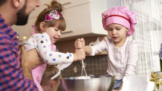 Daughters helping father with cooking