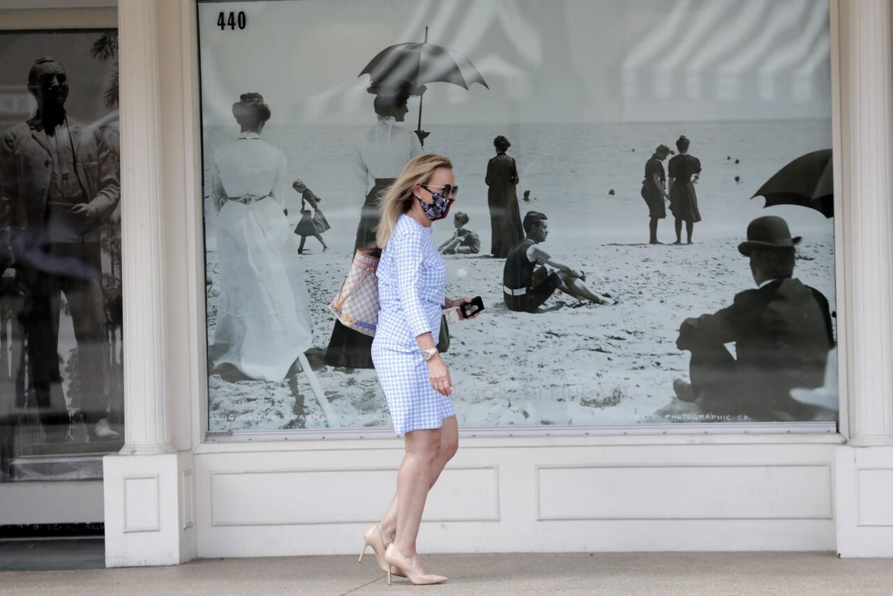 Woman wears mask while walking in Palm Beach