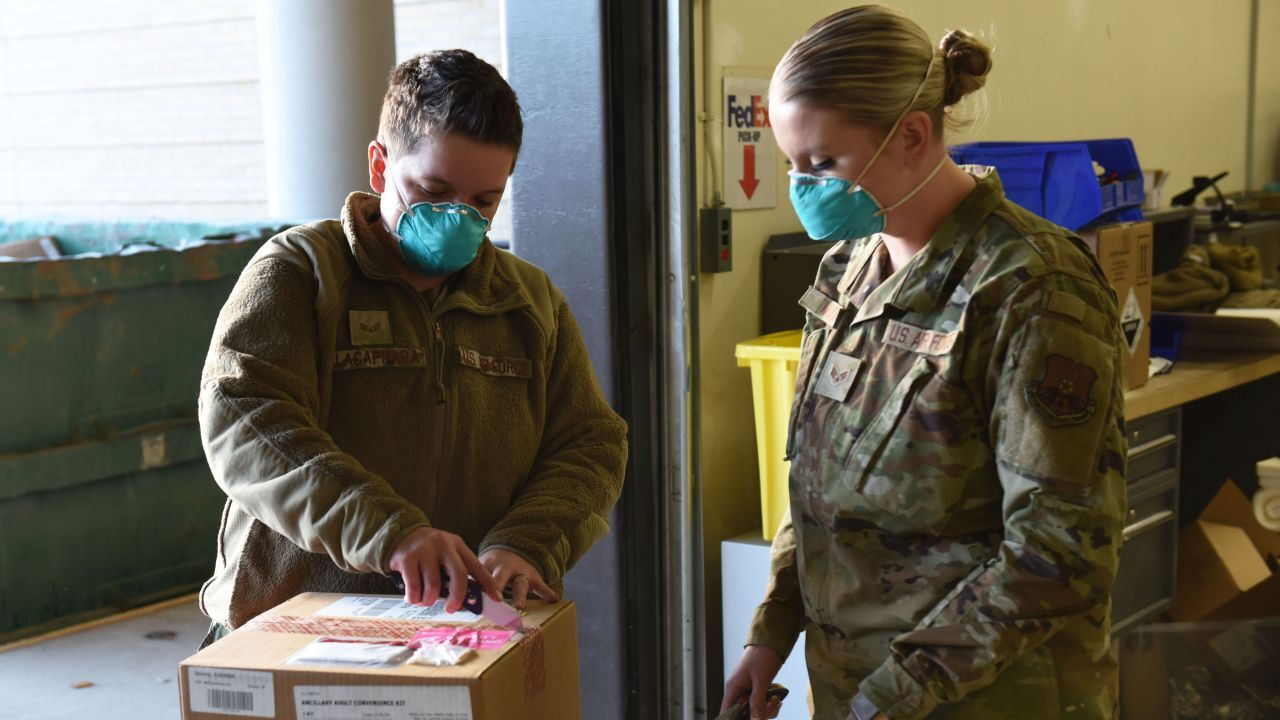 Senior Airmen Lauren Lacaprara, left, and Bayli Moore, 341st Healthcare Operations Squadron medical material technicians, open a shipment of delivered COVID-19 vaccines