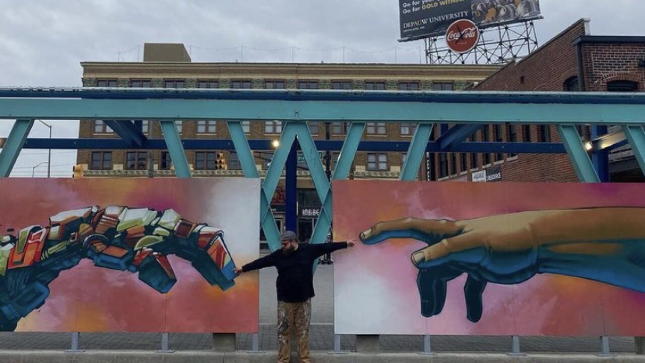 Dan Handskillz standing by his restored mural