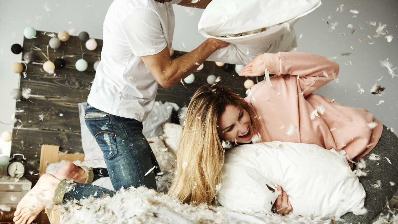 Couple during pillow fight among plumage falling