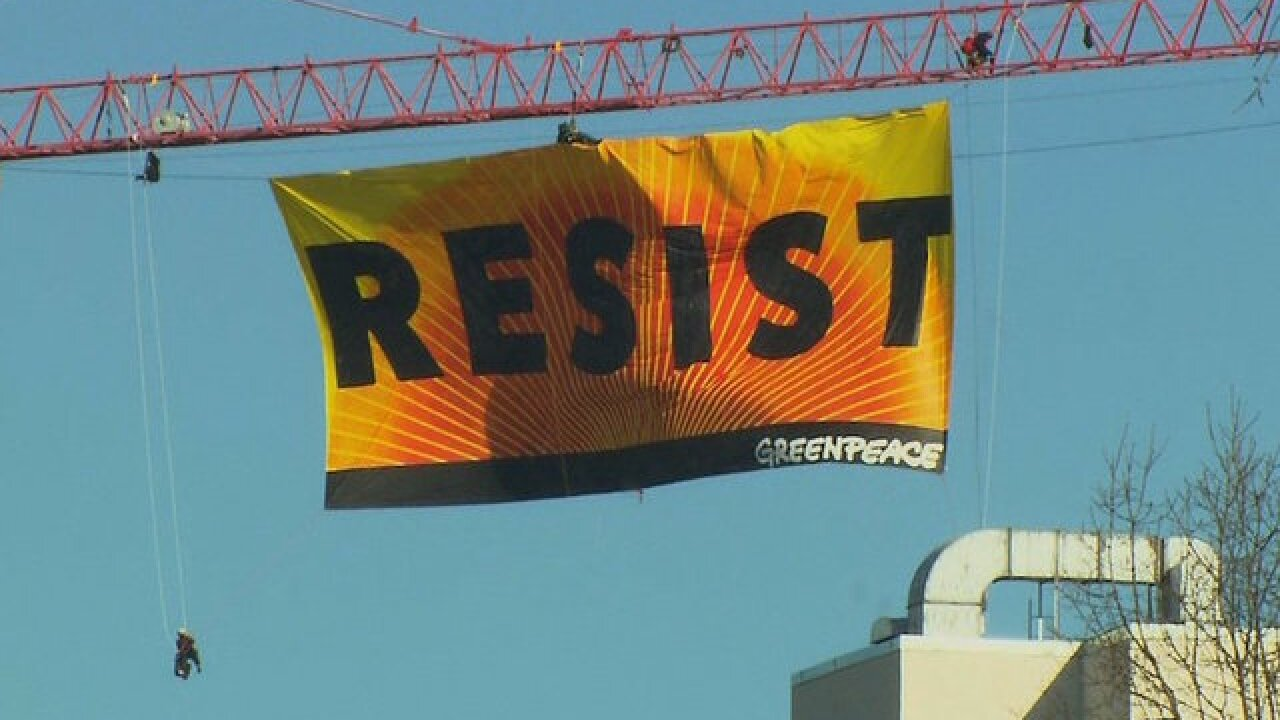 Activists climb construction crane near the White House, unfurl 'resist' banner