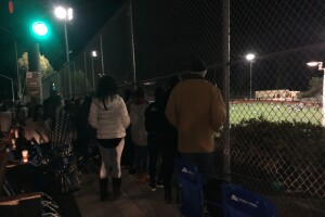 Fans were not allowed to watch from the stands so they peered through a fence along the sidewalk.JPG