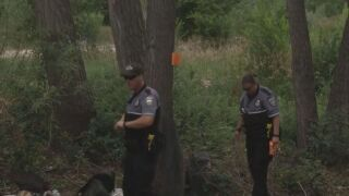 Two officers with the Homeless Outreach Team survey an illegal camp site in Colorado Springs.