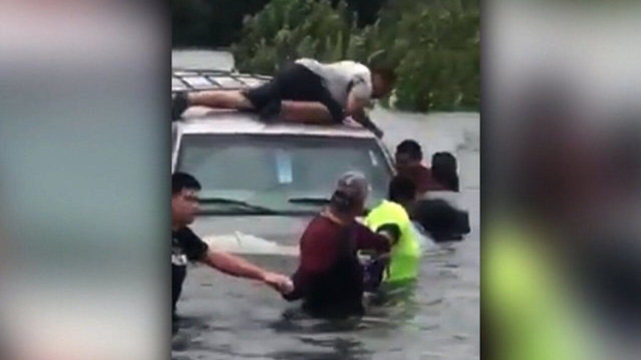 Drivers form a human chain to save a man as floodwaters sweep away his SUV