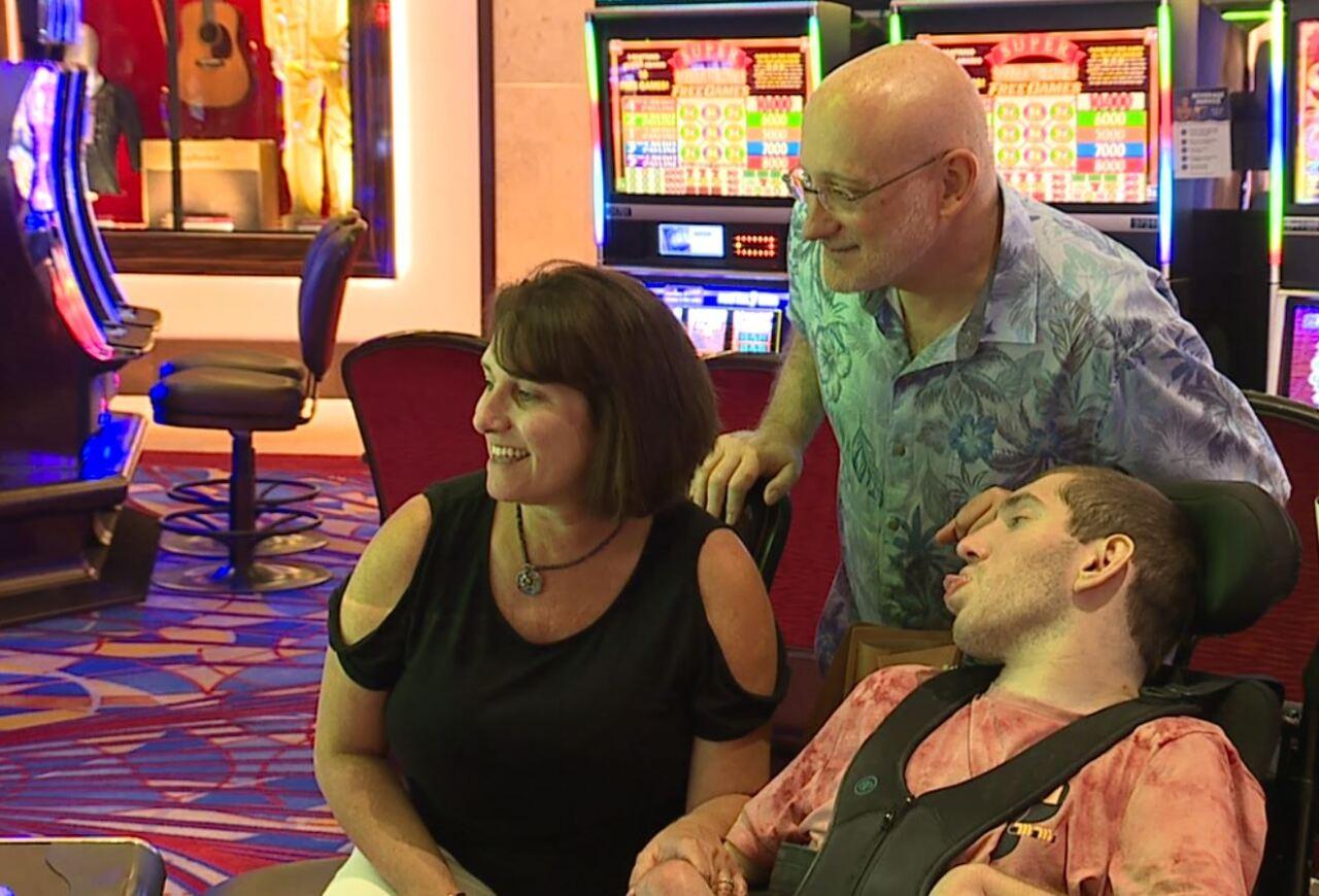 Alexia, left, Scott, center, and Ethan Kadish, right, play a Tarzan-themed slot machine.