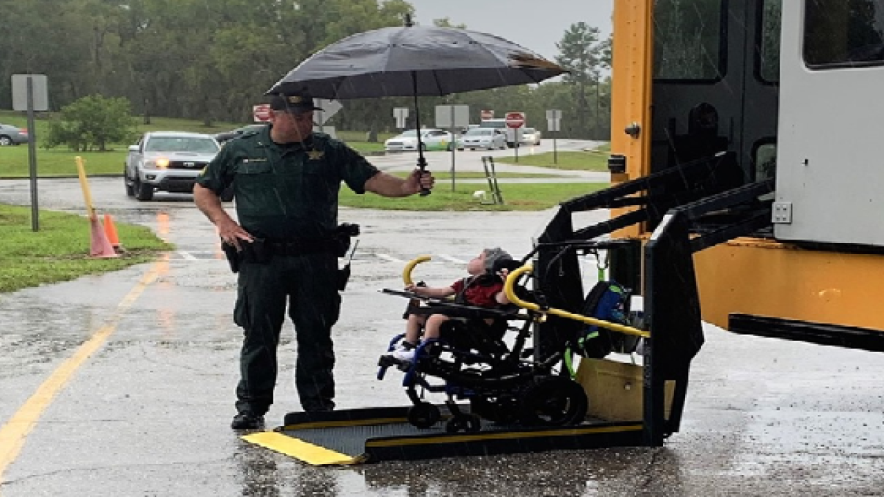 Florida deputy shields student in wheelchair from rain in sweet moment.png