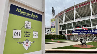 """A green sign reading, """"Welcome Back!"""" and """"Cover Your Bases,"""" sits outside the main entrance to Great American Ball Park."""
