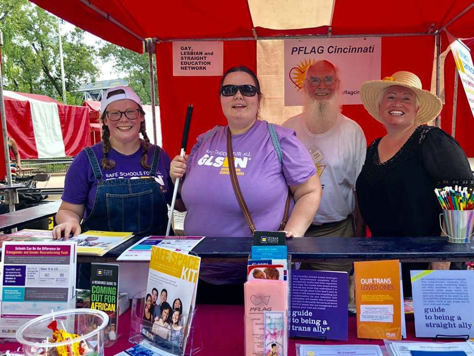 Four volunteers with GLSEN Greater Cincinnati pose at an outdoor event at a booth with pamphlets about the services the nonprofit organizations offers.