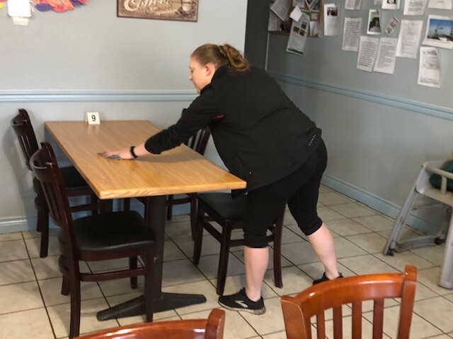 Manager wipes down table and chairs