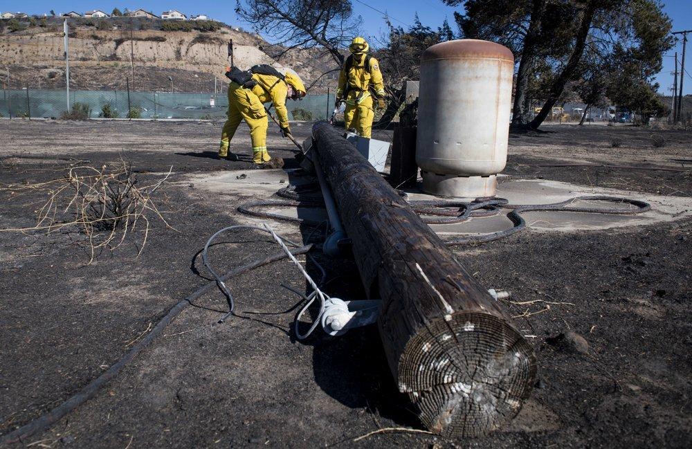 Firefighters with Cal Fire examine a burned down low voltage power pole during the Tick Fire, Thursday, Oct. 25, 2019, in Santa Clarita, Calif. An estimated 50,000 people were under evacuation orders in the Santa Clarita area north of Los Angeles as hot, dry Santa Ana winds howling at up to 50 mph (80 kph) drove the flames into neighborhoods (AP Photo/ Christian Monterrosa)