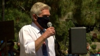 """A city council member in suburban Phoenix is drawing criticism from the governor and others after invoking George Floyd's dying words of """"I can't breathe"""" during a protest over an order to wear masks to stop the spread of coronavirus."""