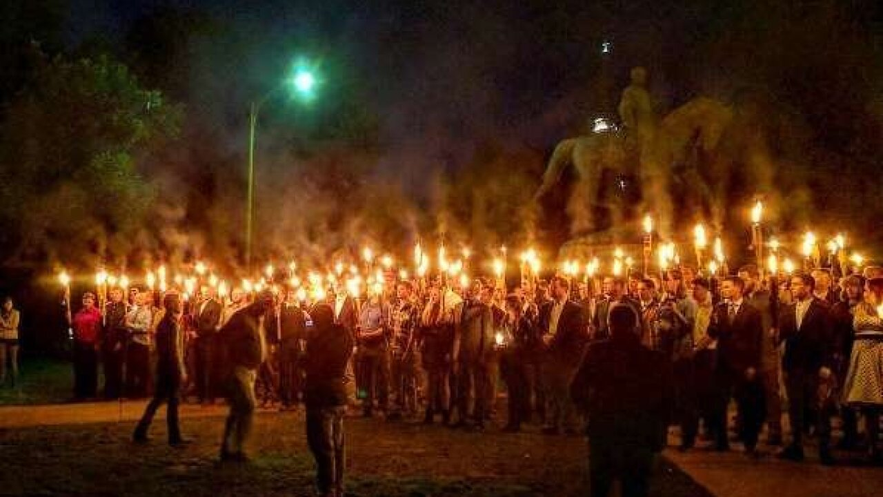 Crowd carrying torches protests removal of Confederate monument at Charlottesville park