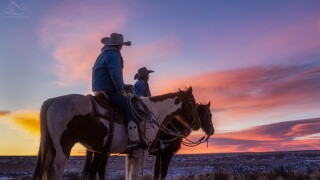Cowboy and cowgirl watching the sunset in Westcliffe