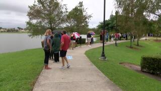 People waiting in rain on first day of early voting outside Spanish River Library