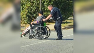 Cpl. Maloy stops traffic to help a pedestrian in a wheel chair cross the street