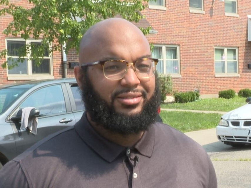 Carlton Collins is wearing a gray shirt in this photo. He has a beard and mustache and a shaved head.