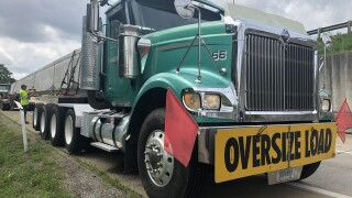 """A green semi-trailer truck is parked on the shoulder of an interstate off-ramp. Two red flags are attached to the truck's front fender, along with a yellow sign, reading """"Oversize load."""" A worker wearing a neon yellow shirt stands in the background."""