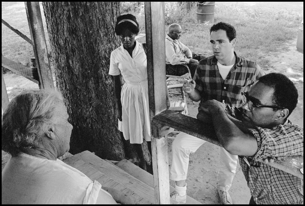 Bob Moses, right, listens intently in this undated photo taken during his days as a civil rights organizer. In the photo, he and two other young organizers are gathered talking with an older person.