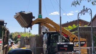 Crews use front end loader to remove junk from yard