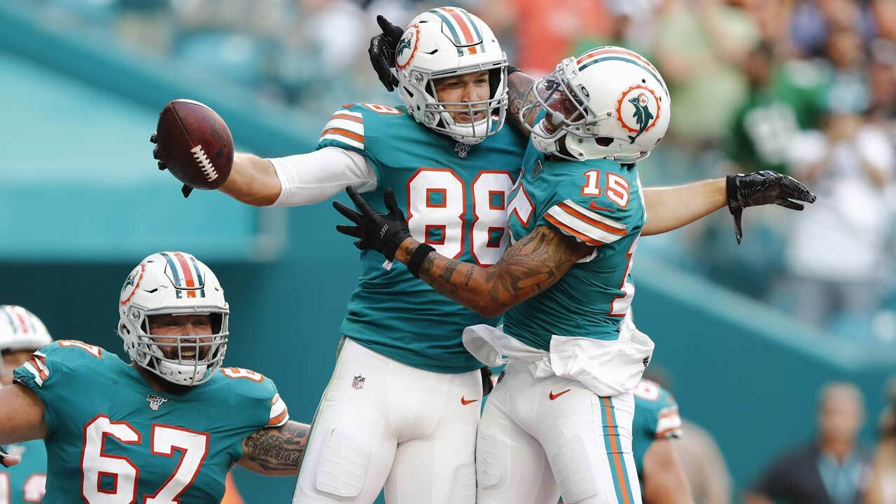 Miami Dolphins wide receiver Albert Wilson (15) congratulates tight end Mike Gesicki (88) after Gesicki scored a touchdown, during the second half at an NFL football game against the Philadelphia Eagles, Sunday, Dec. 1, 2019, in Miami Gardens, Fla. To the left is Miami Dolphins center Daniel Kilgore (67).