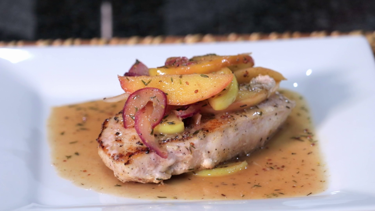 The plated Pork Chops topped with Maple-Dijon Apples.