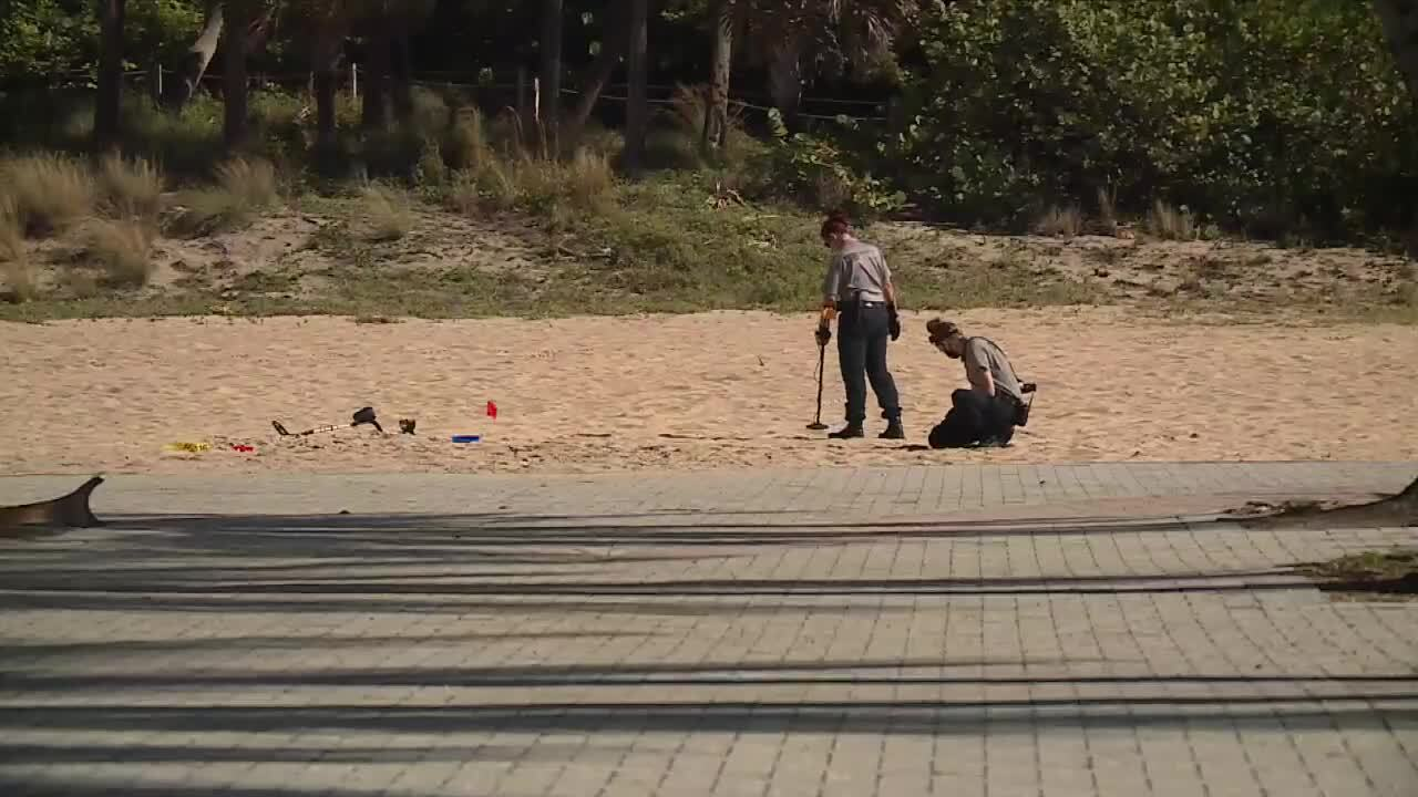 Police use metal detector to search sand after shooting on Singer Island