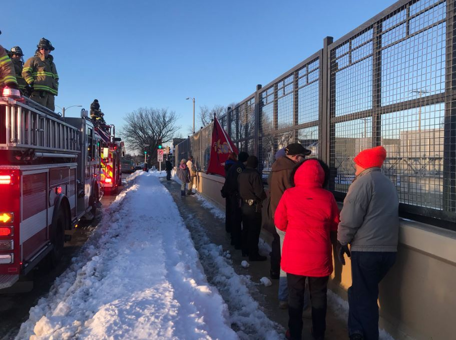 Milwaukeeans gather to pay their respects along the procession route of Officer Matthew Rittner