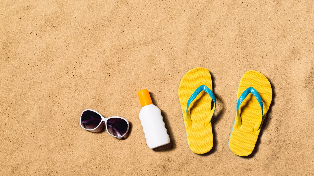 Summer vacation composition. Flip flops, sunglasses and sunscreen.