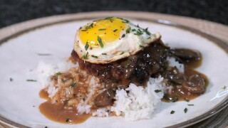 The finished Hawaiian Loco Moco, served with rice and a fried up on top, garnished with chopped parsley.