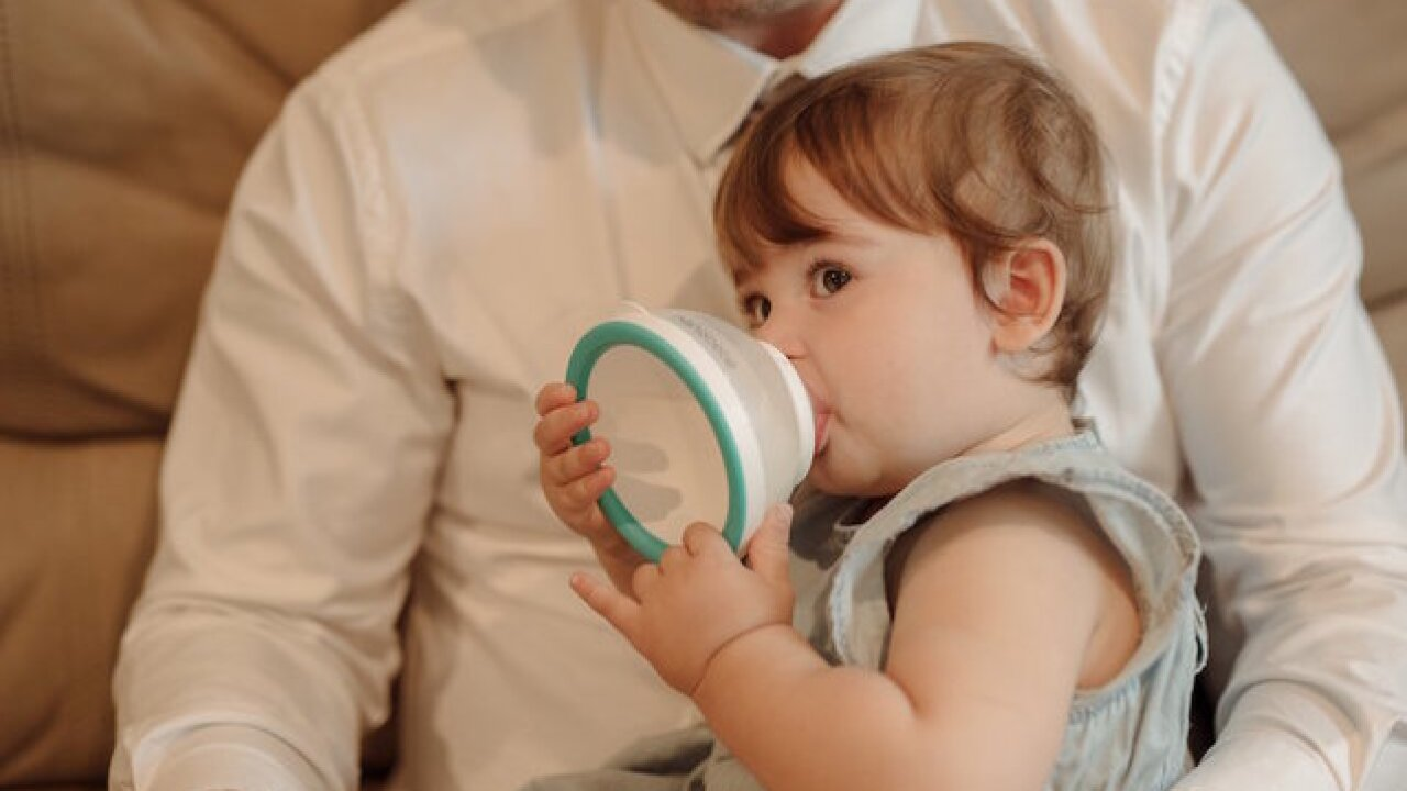 New style of baby bottle invented by tired dad with hungry infant waiting for warm breast milk