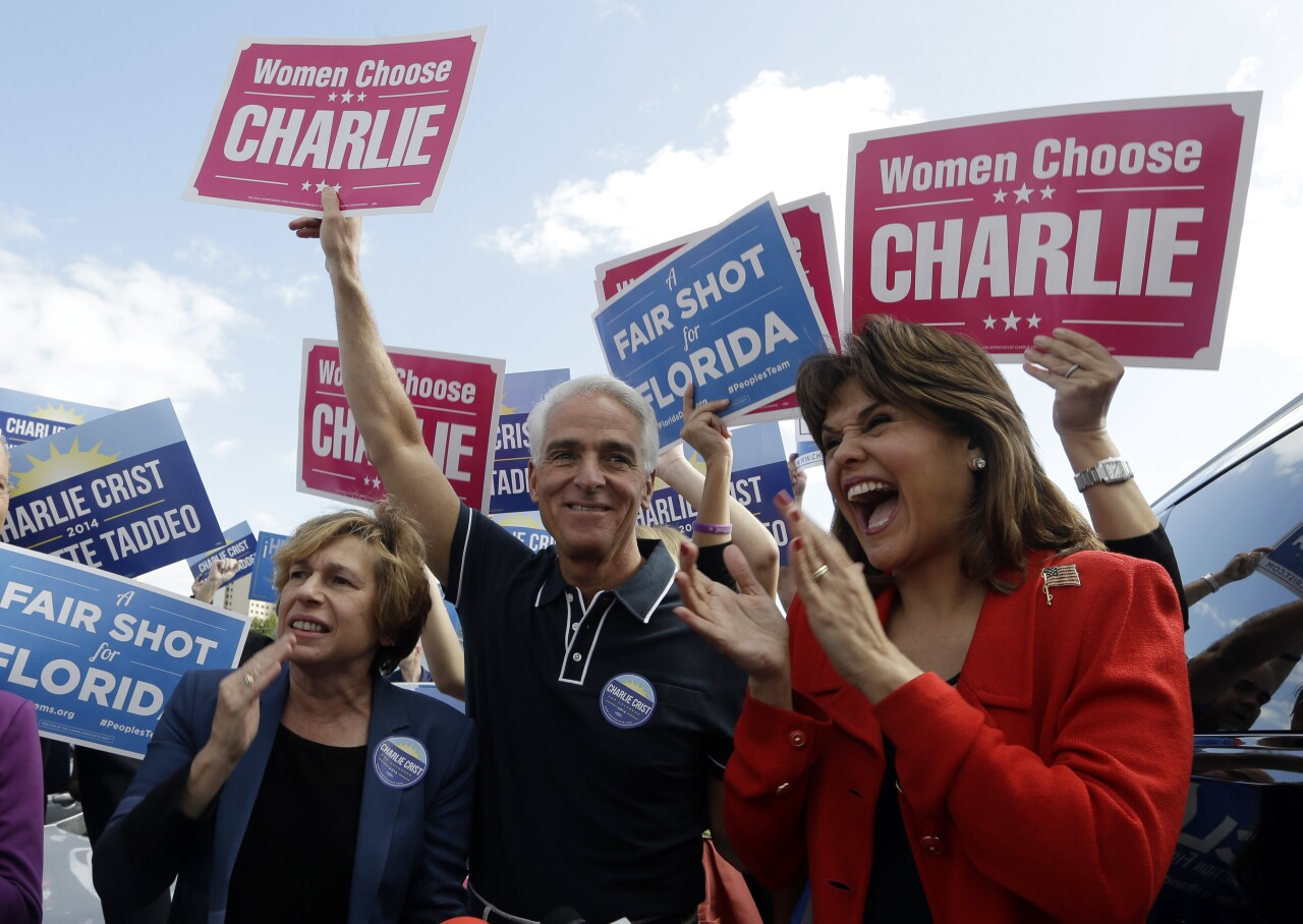 Charlie Crist holds 'Women Choose Charlie' sign in Miami in 2014