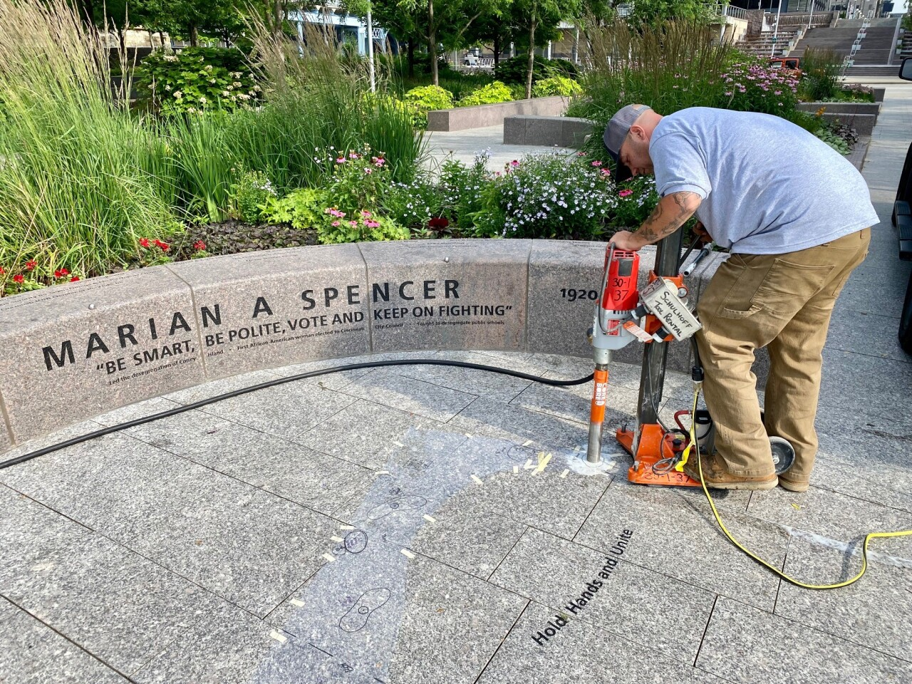 A worker prepares the area in Cincinnati's Smale Riverfront Park where a life-sized sculpture of Marian Spencer will be dedicated on June 27, 2021.