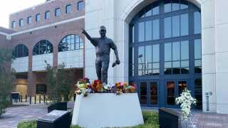 Flowers adorn Bobby Bowden statue outside Doak S. Campbell Stadium at Bobby Bowden Field, Aug. 14, 2021