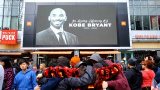 Fans of Kobe Bryant mourn in front of his image at the LALive area across from Staples Center, home of the Los Angeles Lakers, after word of the Lakers star's death in a helicopter crash, in downtown Los Angeles Sunday, Jan. 26, 2020.